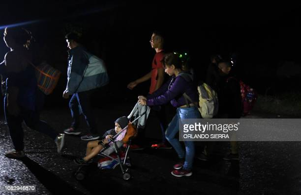 A woman pushes a baby in a stroller as Honduran migrants part of the second caravan to the United States leave San Pedro Sula 180 km north of...