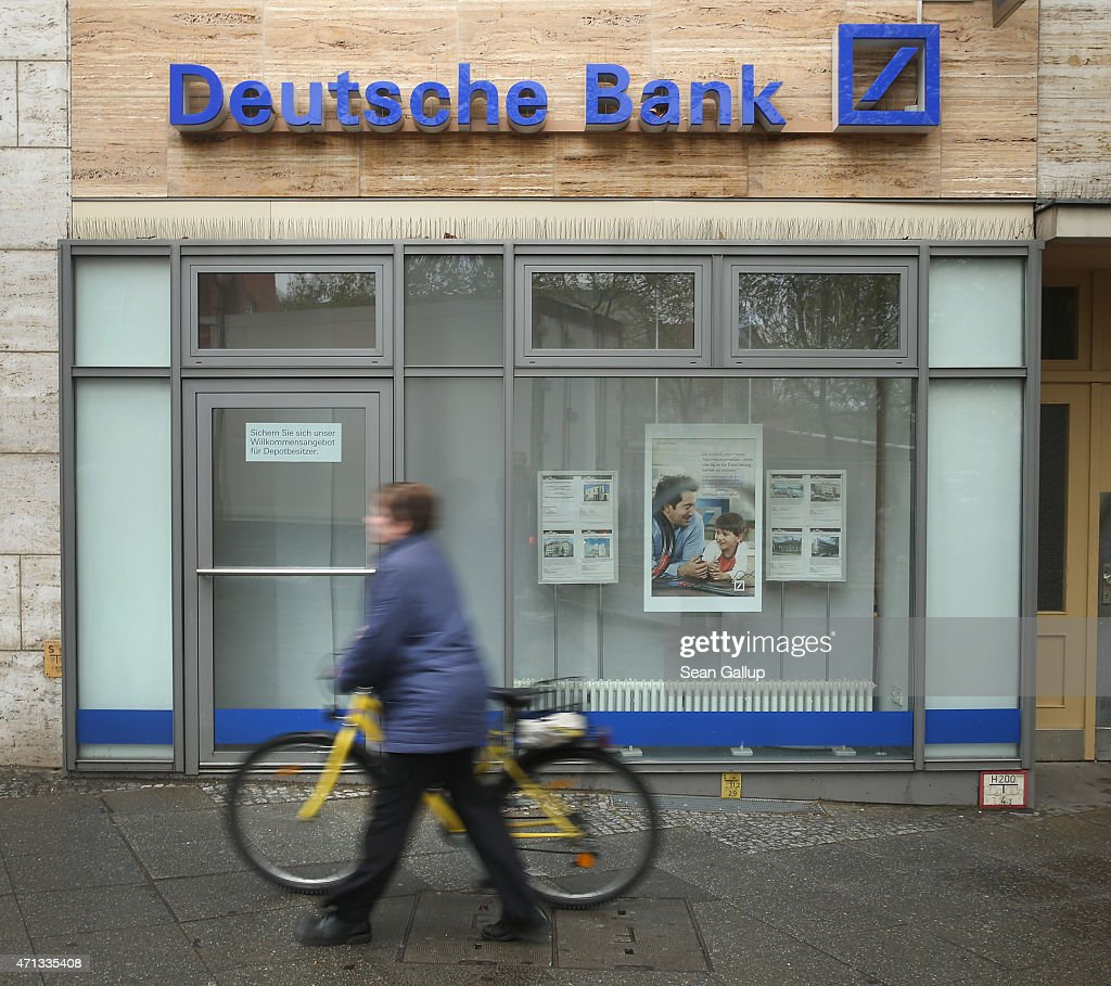 A woman pushes a bicycle past a branch of German bank Deutsche Bank on April 27, 2015 in Berlin, Germany. Deutsche Bank announced earlier in the day that it will close 200 of its 700 branches in Germany over the next two years in an effort to save an annual EUR 3.5 billion.