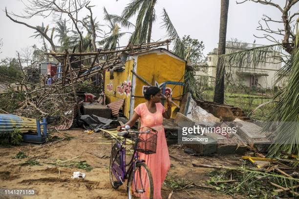 A woman pushes a bicycle past a damaged store after Cyclone Fani passes in the Puri district of Odisha India on Saturday May 4 2019 A category 4...