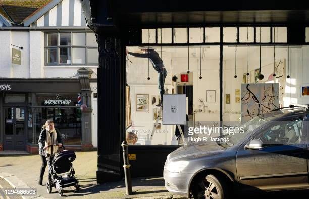 Woman pushes a buggy past a shop in an empty street on January 5, 2021 in Falmouth, United Kingdom. The British Prime Minister made a national...