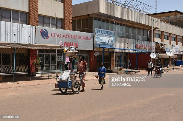 A woman pushes a cart past closed shops in Ouagadougou on September 22 2015 Burkina Faso's coup leader Gilbert Diendere said on September 22 that he...