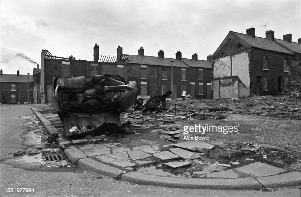 Woman pushes a child in a pram along Walton Street beside fire-damaged and derelict bricked-up terraced houses and the wreckage of burnt-out cars...