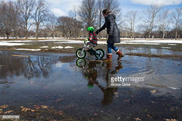 A woman pushes a child on a bike through puddles of water left from melting snow on the Dudley White Bike Path along the Charles River in Cambridge...