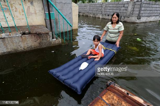 A woman pushes a child through flood waters caused by a passing typhoon in Malabon Metro Manila on June 21 2011 Philippine Atmospheric Geophysical...
