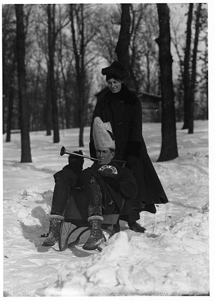 A woman pushes a man in a sled who is wearing a Saint Paul Athletic Club playing a toy horn through St Anthony Park on their way to the St Paul...