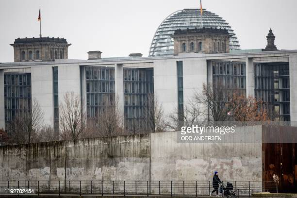 Woman pushes a pram along a concrete wall on Ludwig Erhard Ufer along river Spree on January 9, 2019 near the German parliament in Berlin. - Rain and...