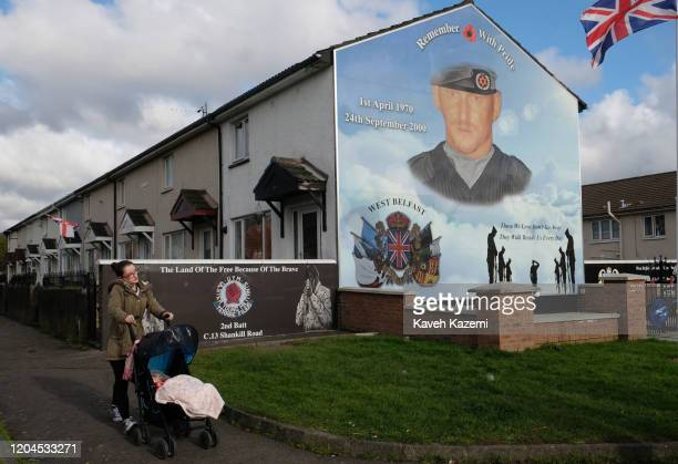 A woman pushes a pram going past the memorial site of Stevie McKeag also known as TopGun who was a Loyalist paramilitary commander of Ulster Defence...