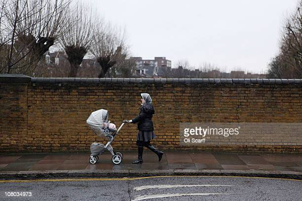 Woman pushes a pram in the Stamford Hill area of north London on January 12, 2011 in London, England. The residents of Stamford Hill are...