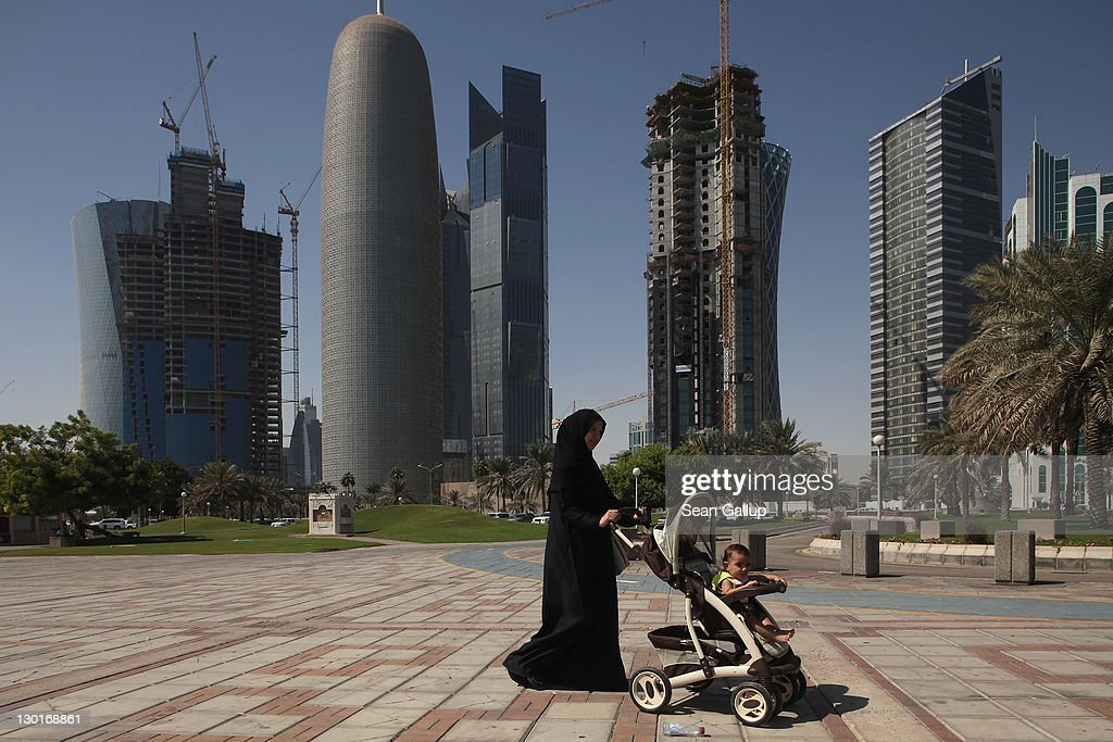 A woman pushes a pram near new office skyscrapers in the budding new financial district on October 23, 2011 in Doha, Qatar. Qatar will host the 2022 FIFA World Cup football competition and is slated to tackle a variety of infrastructure projects, including the construction of new stadiums.