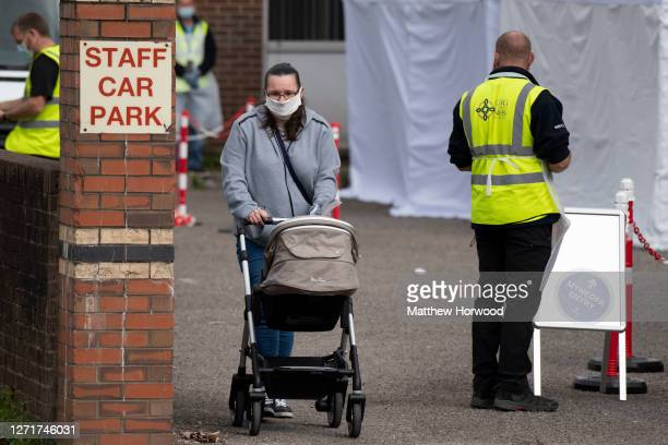 Woman pushes a pram out of a temporary coronavirus testing centre at the Oldway House Car Park on September 10, 2020 in Porth, Wales. A temporary...