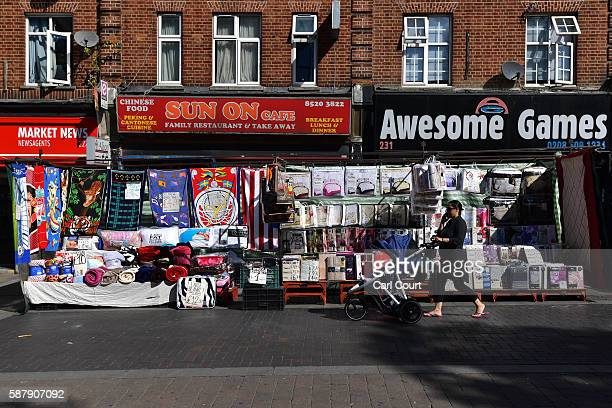 A woman pushes a pram past a stall in Walthamstow market on August 9 2016 in London England Walthamstow Market in north east London is believed to be...
