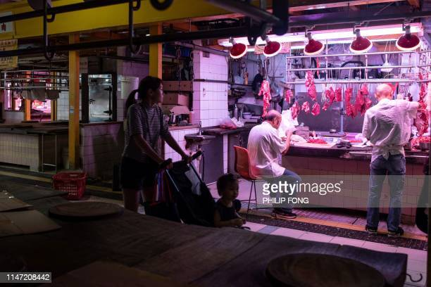 A woman pushes a pram past a stall selling beef as other pork stalls are shuttered inside a market in the Tai Po district in Hong Kong on June 1 2019...