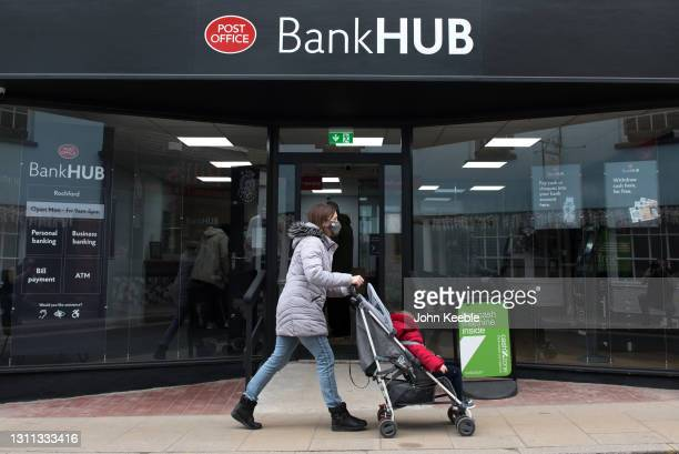 Woman pushes a pram past the new Bank Hub on April 7, 2021 in Rochford, England. The new shared 'Banking Hub' organised by the 'Community Access to...