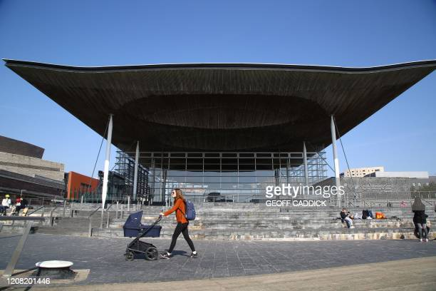 Woman pushes a pram past the Senedd Building in Cardiff Bay, south Wales on March 24, 2020 after Britain's government ordered a lockdown to slow the...
