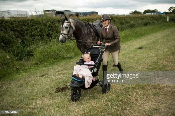 TOPSHOT A woman pushes a pushchair as she leads a horse adjacent to a showjumping ring on the first day of The Royal Cheshire County Show at Tabley...