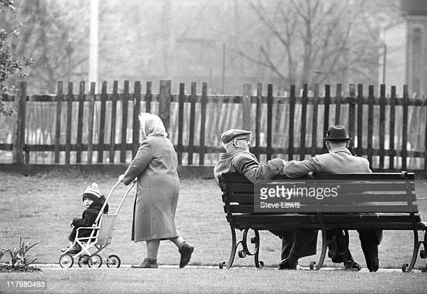 Woman pushes a pushchair past two men on a park bench in London's East End, circa 1970.