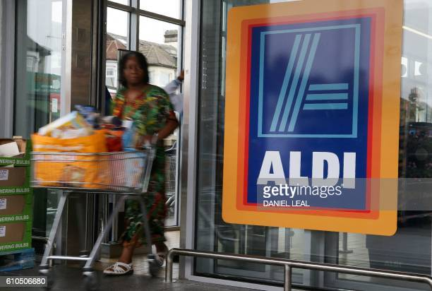 A woman pushes a shoping trolley past an Aldi logo as she leaves one of the company's supermarket stores in London on September 26 2016 Aldi UK...