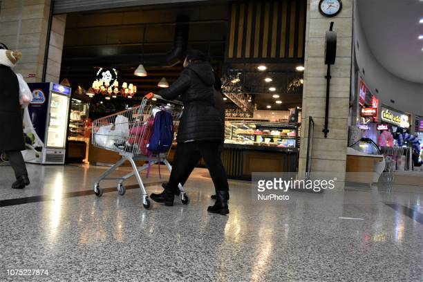 A woman pushes a shopping cart at a shopping center in Ankara Turkey on December 27 2018 A year is passed under economic difficulties as part of high...