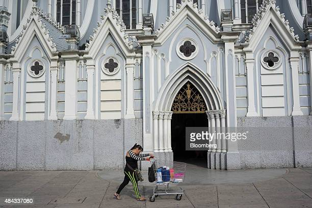 A woman pushes a shopping cart past La Ermita Church in Cali Colombia on Wednesday Aug 12 2015 Colombia's central bank last month cut its forecast...