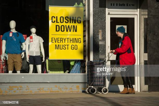 A woman pushes a shopping trolley past a clothing retailer advertising a closing down sale on High Row in the town centre of Darlington northeast...