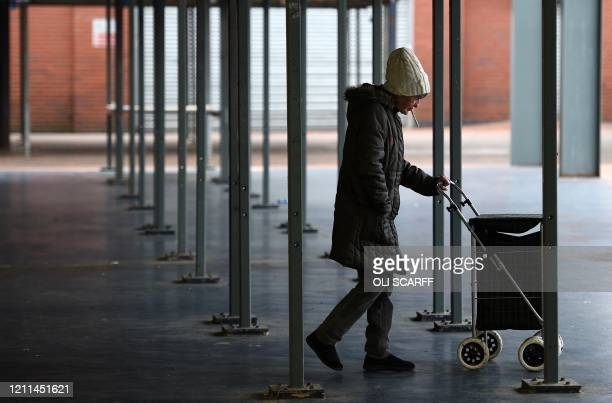 Woman pushes a shopping trolley through a closed market in Manchester, north west England, on May 1 as life in Britain continues during the...