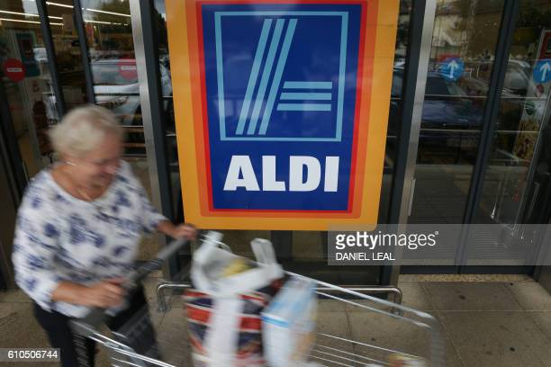A woman pushes a shoppping trolley as she leaves an Aldi supermarket store in London on September 26 2016 Aldi UK announced on Monday that it will...