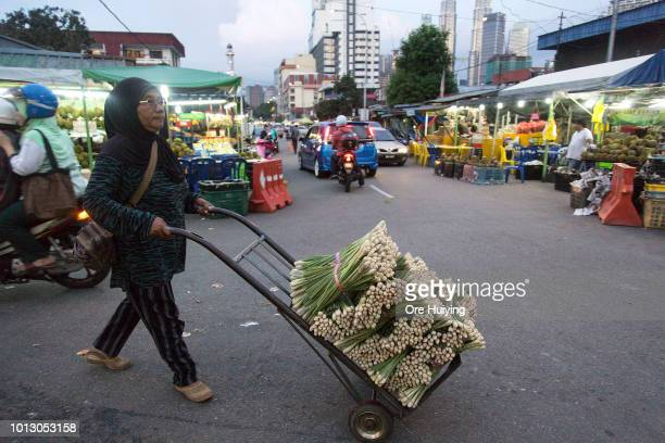 A woman pushes a stack of produce on the street of a market on July 30 2018 in Kuala Lumpur Malaysia Malaysia's former prime minister Najib Razak has...