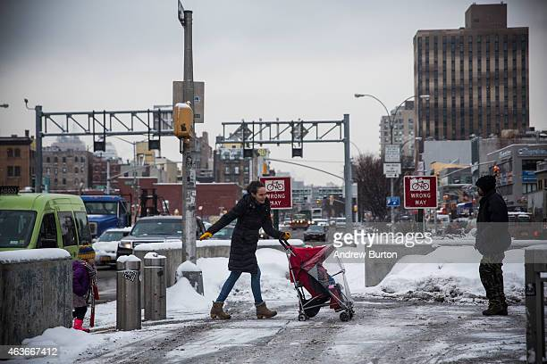 A woman pushes a stroller across the street after a snowstorm on the morning of February 17 2015 in New York City The city received approximately 36...
