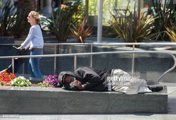 A woman pushes a stroller along while a homeless man sleeps in downtown San Francisco's Union Square in California on June 2016 Homelessness is on...