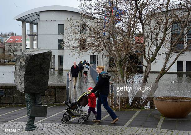 A woman pushes a stroller as she passes the City Hall polling station in Reykjavík Iceland on April 27 2013 Icelanders voted in a general election...