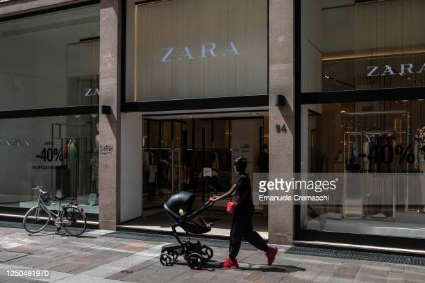 Woman pushes a stroller as she walks past a Zara retail store in a pedestrian street in the Lower Town on June 18, 2020 in Bergamo, Italy. The city...