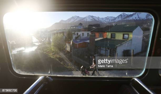 A woman pushes a stroller as viewed from the window of a vintage London Routemaster bus used for tourist tours on November 5 2017 in Ushuaia...