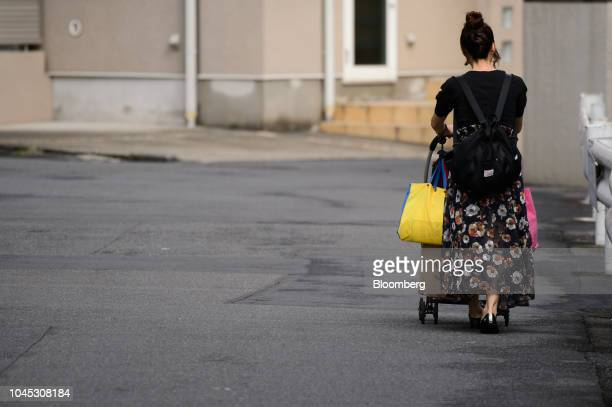 A woman pushes a stroller in Kawasaki Kanagawa Prefecture Japan on Tuesday Sept 18 2018 Japan's population of 127 million isforecast to shrinkby...