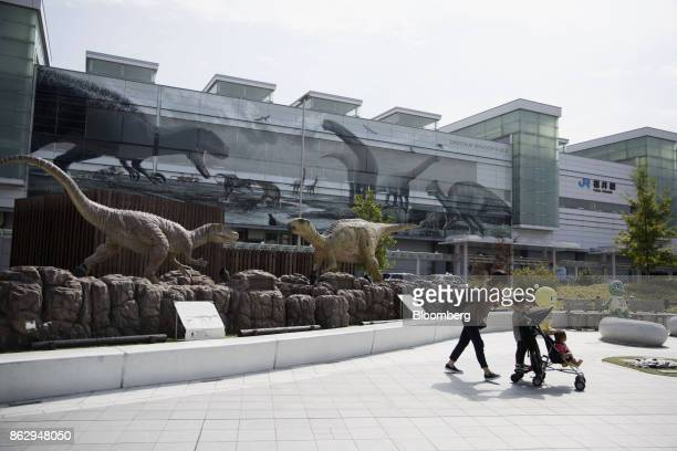 A woman pushes a stroller near lifesize replica dinosaurs in Dinosaur Plaza outside Fukui station in Fukui Japan on Wednesday Oct 11 2017 Fukui...