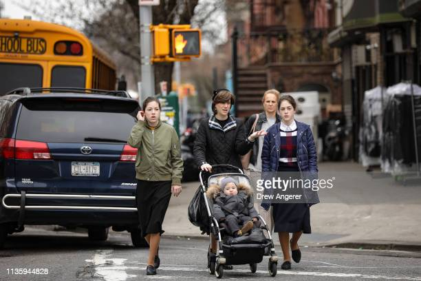 A woman pushes a stroller near the Yeshiva Kehilath Yakov School in the South Williamsburg neighborhood April 9 2019 in the Brooklyn borough of New...
