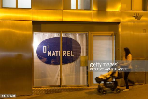 A woman pushes a stroller past the newly opened nudist restaurant o'naturel in Paris on December 5 2017 Leave your coats your pants and your...