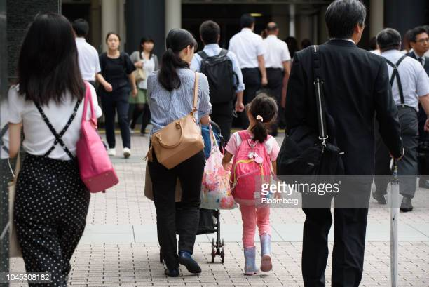 A woman pushes a stroller while walking with a girl along a sidewalk in Kawasaki Kanagawa Prefecture Japan on Tuesday Sept 18 2018 Japan's population...