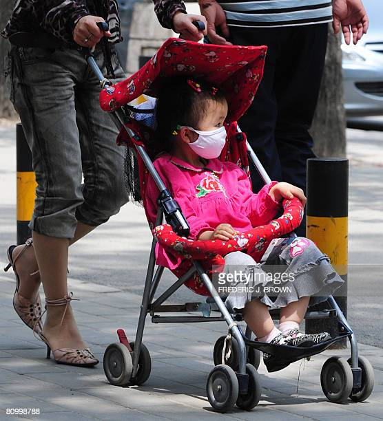 A woman pushes a stroller with as a child wears a face mask near a children's hospital in Beijing on May 6 2008 Ten doctors and officials in China...