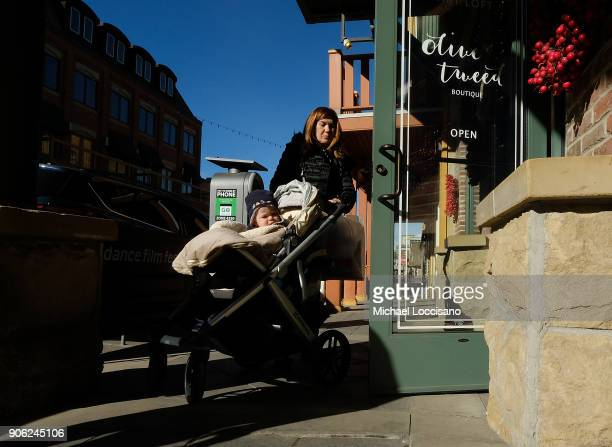A woman pushes a toddler in a stroller up Main Street as Park City prepares for the 2018 Sundance Film Festival on January 17 2018 in Park City Utah