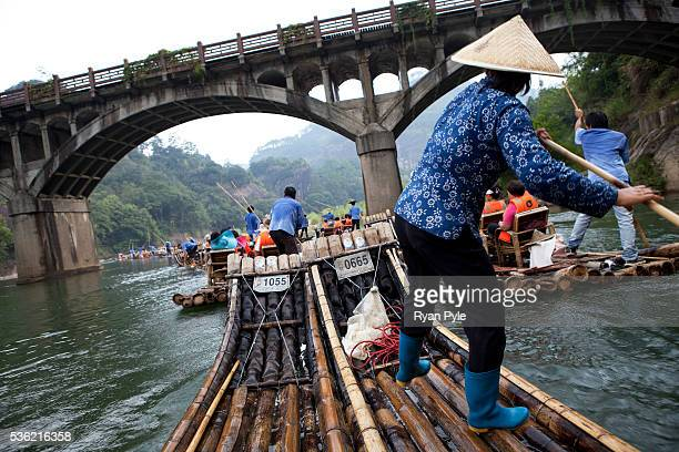 A woman pushes a tourist boat along the Nine Twists River in the Wuyi Mountain provincial park in southern China's Fujian province | Location Wuyi...