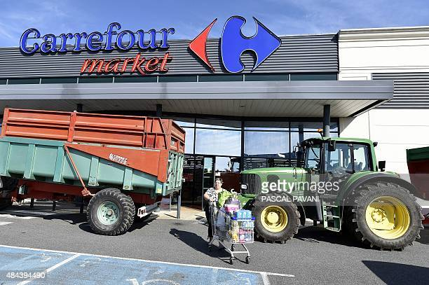 A woman pushes a trolley between two tractors outdoor a supermarket where farmers did a prices and origins checking operation on meats and dairy...