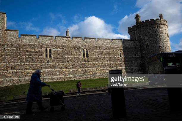 A woman pushes a trolley in front of Windsor Castle on January 5 2018 in Windsor England British Prime Minister Theresa May has publicly challenged...