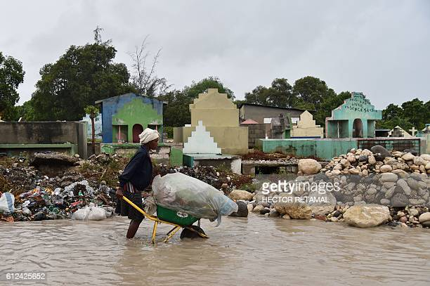 TOPSHOT A woman pushes a wheelbarrow while walking in a partially flooded street in the Haitian capital PortauPrince on October 4 2016 Hurricane...