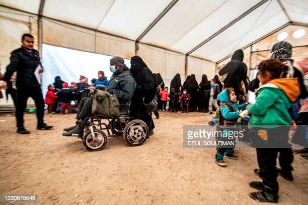 Woman pushes a wheel-chair bound man clad in surgical mask during the release of persons suspected of being related to Islamic State group fighters...
