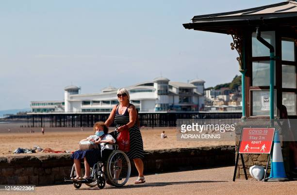 Woman pushes an elderley lady wearing PPE , including a face mask as a precautionary measure against COVID-19, in a wheelchair past a sign advising...
