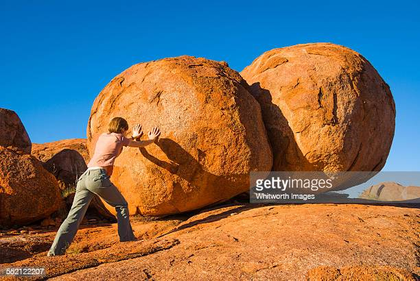 Woman pushes Devil's Marbles in Australian outback