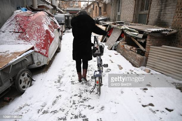 A woman pushes her bicycle in an alley after a snowfall in Beijing on February 12 2019