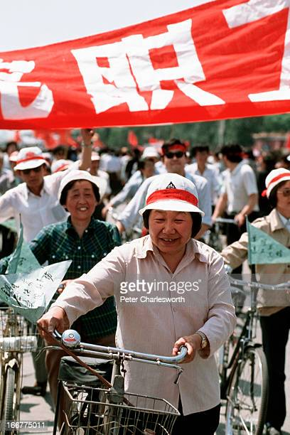 A woman pushes her bicycle in front of a protest banner as she and thousands of other prodemocracy demonstrators march past Tiananmen Square...