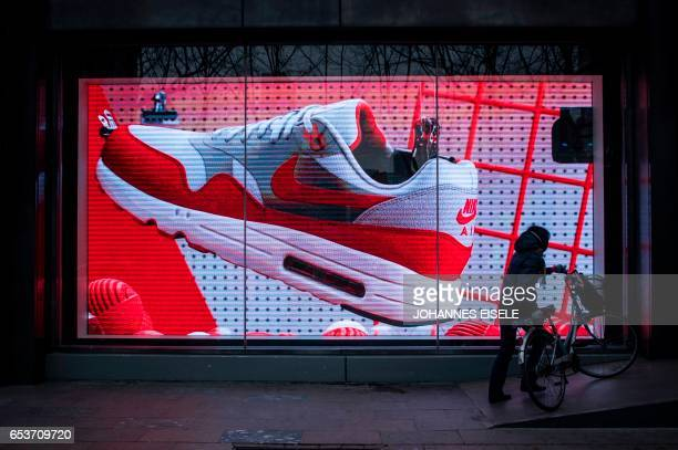 Woman pushes her bike next to the flagship store of sporting-goods giant Nike in Shanghai on March 16, 2017. US sporting-goods giant Nike has become...