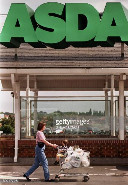A woman pushes her child and groceries outside the Asda supermarket in London's Southgate area 14 June 1999 Asda Britain's third largest supermarket...